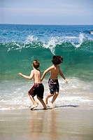 two boys running from a wave