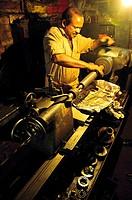 A machinist using a metal lathe in a dark workshop  Kollam, Kerala, India
