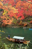 A pleasure boat being poled along the pond in Arashiyama under red-orange autumn maple leaves