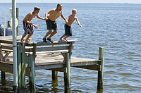 Grandfather jumping from dock with grandsons