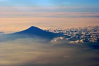 A volcanic mountain peak rising above the clouds in early morning light