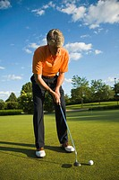 GOLF Adult middle aged male practice putting on green at public course in Deerfield, Illinois, swing putter
