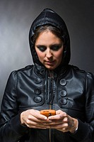 Woman with leather jacket and hood using mobile phone