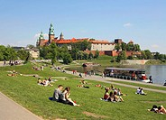 Poland, Krakow, people resting by Vistula river, Wawel Hill