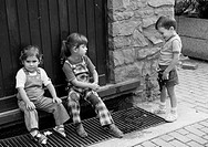 Seventies, black and white photo, humour, people, children, two little girls sit in front of a street door the feet on a drain grate, little boy stand...