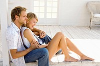 Young couple happy sitting on the floor