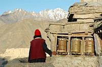 Tibetan woman spinning prayer wheels Lama Yuru, Ladakh, India
