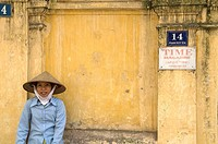 Woman resting on a wall, Hanoi, Vietnam.