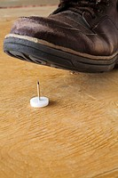 Close-up of an elevated shoe about to step on a jumbo thumbtack on a plywood floor, Studio Composition, Laval, Quebec, Canada
