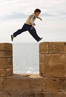Boy jumping on the wall of Essaouira, Marocco