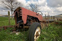 Disused old tractor in field