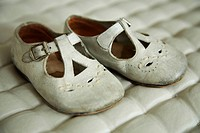 Old baby´s shoes on quilted material