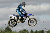 Martin Barr 9 jumps his 450 Yamaha into a cloudy sky thrown up dirt and mud at tandragee motocross circuit, county down northern ireland