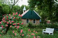 Old church from 1696 surrounded by a garden with a shrub of red roses  Oldest church on East Frisian islands  North Sea  Germany