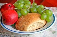 Bread, apples and grapes on plate  Home-baked broccoli bread with green grapes and red apples on plate  Whole grain wheat bread with broccoli  Very go...