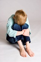 A young boy sits hunched over hugging his bent legs and hiding his face