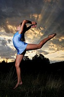 young gymnast jumping in a meadow at dusk