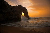 Sun setting through Durdle Door during rough weather and stormy Sea.