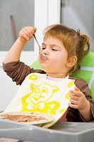 Toddler girl is eating with spoon