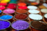 colorful powder pigments in rows in clay bowls