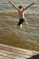 Boy jumping from boat dock into the Albemarle Sound
