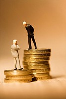 Miniature businessmen standing on coins on financial newspaper  This photo illustrates the vast gap in wages within companies  Senior executives earni...