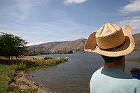 Rear view of man looking out onto lake