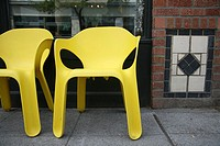 Two yellow chairs by wall
