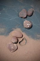 A grouping of six rocks imbedded into beach sand with the impression of one rock missing.