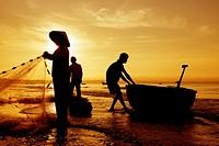 Silhouetted fishermen on Mui Ne Beach in Vietnam