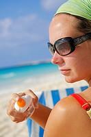 Woman in sunglasses applying suntan lotion on a Caribbean beach