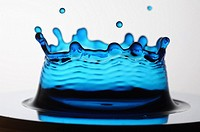 A single drop of blue liquid forming a coronet as it lands