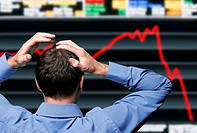 Stocktrader Clutching His Head in Front of a Screen Showing a Stock Market Crash