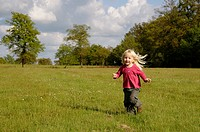 Stock photo of a blond haired 3 year old girl running in a field