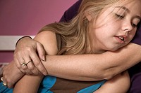 Blond preteen girl leaning against her mother