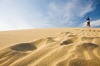 Woman at the top of a sand dune with her footprints in the foreground