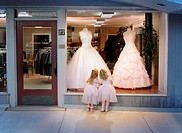 2 girls standing at window looking at gowns dreaming about a dance
