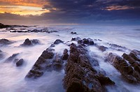 The incoming tide washing over the rocks at dusk at Westward Ho! in Devon, England