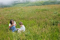 Boy and girl playing on a meadow in the mountains of Somiedo