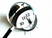 Magnifying glass over clock about to strike twelve´o´clock