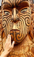 Maori carving, a tourist´s hand feels texture of face, Rotorua, New Zealand