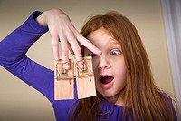 Preteen redhead girl with mousetraps on her fingers