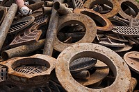 Pile of Assorted Rusted Manhole and Sewer Covers made of Ferous Metal at a Scrap Metal Recycling Junkyard, Quebec, Canada