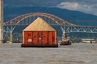 Canada, BC, New Westminster  Load of wood chips being towed up the Fraser River  Patullo Bridge and Skytrain Bridge in background