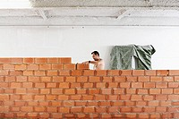 man working in a wall of bricks