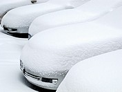 Parked cars buried in snow.