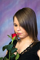 Studio, UK, Europe  Young woman smelling a red rose