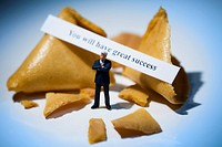 Miniature businessman in front of fortune cookies with message reading you will have great success