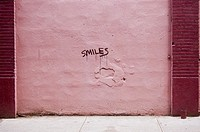 The word ´smiles´ is written on a pink wall