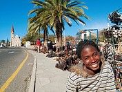 Namibia - Vendor at the well-known open-air souvenir market in the centre of Namibia´s capital Windhoek with the famous Christuskirche Church of Chris...